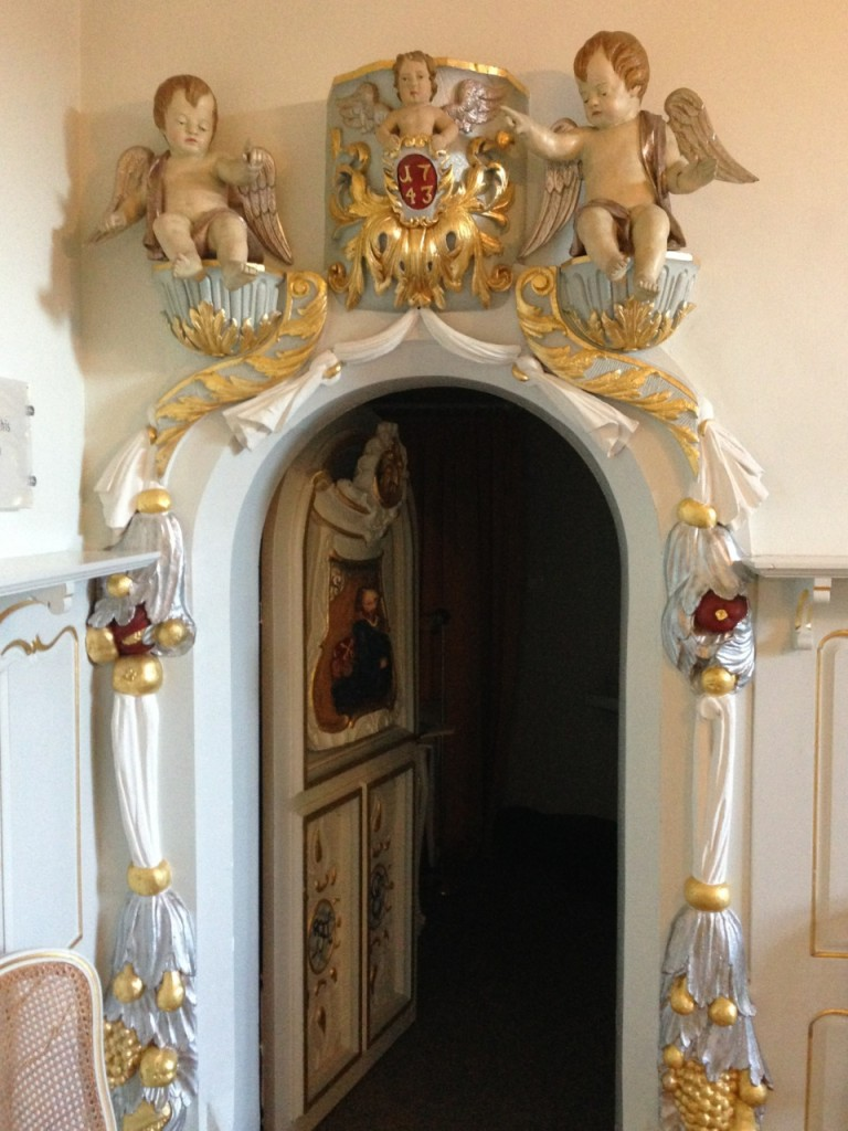 small ornate doorway decorated with naked cherubs and a shield with 1743 on it